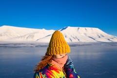 Close-up van een meisje in een regenboogjasje en geel gebreid GLB op de achtergrond Svalbard Longyearbyen van het bergnoorden p stock afbeeldingen