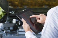 Close-up van een mens die de auto controleren op touchscreen tablet in een garage Stock Fotografie