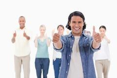 Close-up van een mens die met zijn duim-omhooggaand met erachter mensen glimlachen Stock Afbeeldingen