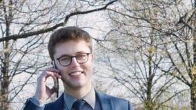 Close-up van een mens die op de telefoon met een glimlach en het drinken koffie spreken stock videobeelden