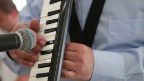 Close-up van een mens die op het muzikale instrument Melodica spelen stock footage
