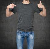 Close-up van een mens die zijn vinger op een lege grijze t-shirt, andere hand benadrukken de duim Stock Foto