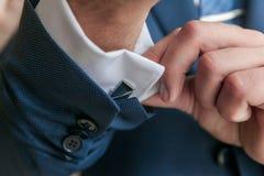 Close-up van een mens in een tux die zijn cufflink bevestigt cufflinks van de bruidegomvlinderdas stock foto's