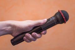 Close-up van een mensen` s hand die een zwarte microfoon op een sinaasappel houden stock fotografie