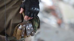 Close-up van een militair in tactische handschoenen met een granaat in een zak stock footage