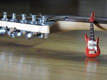 Close-up van een miniatuur elektrische gitaar die op een elektrisch gitaarwapen leunen royalty-vrije stock afbeeldingen
