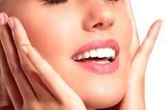 Close-up van een mooi model wat betreft haar perfect huidgezicht Royalty-vrije Stock Foto's
