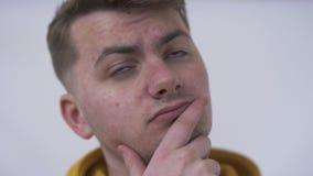 Close-up van een nadenkende jonge mens die weg en bij de camera kijken De kerel die alvorens het besluit te nemen denken emoties stock video