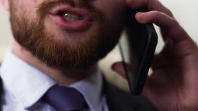 Close-up van een niet geïdentificeerd mannelijk gezicht die op een celtelefoon spreken stock footage