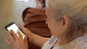 Close-up van een oude vrouw die een smartphone gebruiken aan menings sociale netwerken stock footage