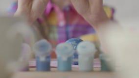 Close-up van een paasei dat enkel door een weinig mooi meisje wordt geschilderd Voorbereiding van de Pasen stock footage