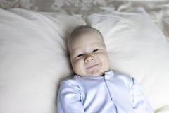 Close-up van een pasgeboren baby die op een bed in blauwe kleren liggen stock foto
