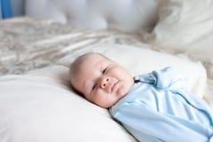 Close-up van een pasgeboren baby die op een bed in blauwe kleren liggen stock fotografie