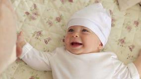 Close-up van een pasgeboren jongen in een witte hoed die op een bed thuis met teddybeer liggen stock footage
