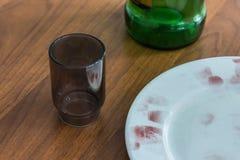 Close-up van een plaat, een glas, een fles op een houten lijst bij de misdaadscène De vingerafdrukken op de rand van de schotel z stock afbeeldingen