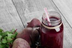Close-up van een plantaardige smoothie Rode bietendrank in een kruik op een houten lijstachtergrond Rijpe gehele bieten en blader Royalty-vrije Stock Fotografie