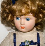 Close-up van een pop van het blondeporselein op witte achtergrond, uitstekend speelgoed stock foto