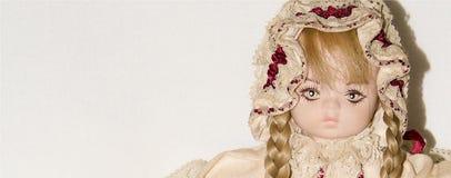 Close-up van een pop van het blondeporselein op witte achtergrond, uitstekend speelgoed wordt geïsoleerd dat stock foto's