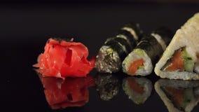 Close-up van een rij van sushi op een zwarte achtergrond stock videobeelden