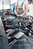 Close-up van een schroevedraaier door een deskundige werktuigkundige wordt gehouden alvorens een motor te herstellen die stock afbeelding