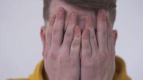 Close-up van een schuwe jonge mens die de camera van achter vingers bekijken die gezicht behandelen met zijn handen Concept het V stock video