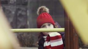 Close-up van een slowmotion meisjesleeftijd 3-4 in warme kleren die zich zorgvuldig op de heldere kleurrijke speelplaats bevinden stock videobeelden