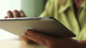 Close-up van een tabletcomputer in vrouwenhanden stock videobeelden