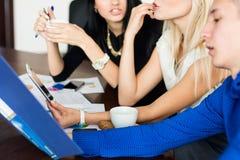 Close-up van een team van jonge bedrijfsmensen die bij de lijst zitten Stock Foto's