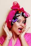 Close-up van een verraste jonge vrouw met haarkrulspelden Stock Foto's