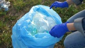 Close-up van een vrijwilligershand die huisvuil in een grote blauwe plastic zak verzamelen Afval het sorteren, milieuconcept stock footage