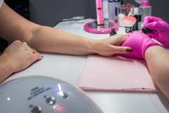 Close-up van een vrouw in een spijkersalon die een manicure ontvangen door een schoonheidsspecialist wordt geschoten die royalty-vrije stock fotografie