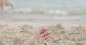 Close-up van een vrouwelijk been met een mooie pedicure in het zand door het overzees stock videobeelden