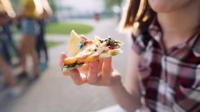 Close-up van een vrouwelijke hand met een plak van vegetarische pizza Ondiepe Diepte van Gebied stock videobeelden
