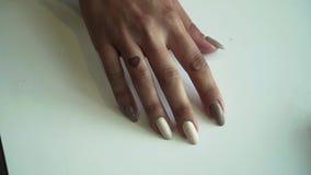 Close-up van een vrouwelijke hand op een lijst met een manicure Het meisje gesturing met haar vingers in anticiperen stock video