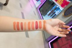 Close-up van een vrouwelijke koper die de geselecteerde kleur van een lippenstift kiezen die op haar huid proberen stock foto's