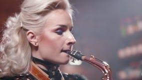 Close-up van een vrouwelijke saxofonist wordt geschoten die een lied uitvoeren dat stock video