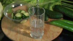 Close-up van een vrouwen gietend water in een leeg glas op een zwarte achtergrond stock video