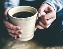 Close-up van een vrouwen` s hand die een kop van hete koffie houdt manier, vrije tijd royalty-vrije stock afbeeldingen