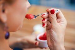 Close-up van een vrouwen` s hand die een kop met eigengemaakt rood roomijs houden Ontbijt, snacks Het concept het gezonde eten en Stock Foto's