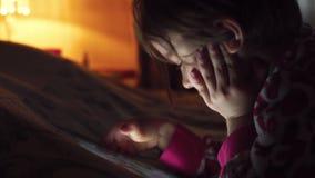Close-up van een weinig leuk meisje in volledige duisternis het letten op tablet stock videobeelden