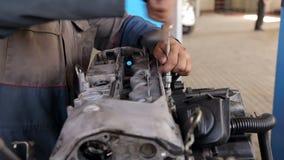 Close-up van een werktuigkundige die de motor van de auto herstellen bij het benzinestation stock footage