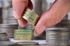 Close-up van een wijsvingerkranen op een stapel van Brits pondmuntstuk Stock Foto