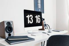 Close-up van een wit bureau met spiraalvormige blocnotes, sprekers en een moderne bureaucomputer in een modieus werkruimtebinnenl stock foto's