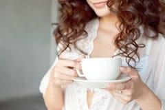 Close-up van een witte Kop van de hete koffie van de lattekunst met een hartvorm in de handen van een jong meisje royalty-vrije stock afbeelding