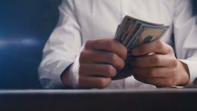 Close-up van een zakenman tellend geld en het slaan van zijn vuist op de lijst Het bedriegen met betaling stock video