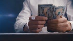 Close-up van een zakenman tellend geld en het slaan van zijn vuist op de lijst Het bedriegen met betaling stock videobeelden