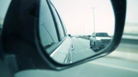 Close-up van een zijachteruitkijkspiegel van auto wordt geschoten die voorraad De mening van de zijaanzichtspiegel van auto's het stock footage