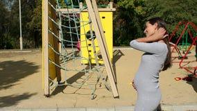Close-up van een zwangere vrouw die haar grote buik strijken dichtbij de speelplaats stock videobeelden