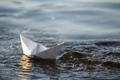 Close-up van eenvoudige kleine witte origamidocument boot die in bl drijven Royalty-vrije Stock Foto