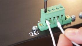 Close-up van elektricienarbeider het schroeven draden stock video
